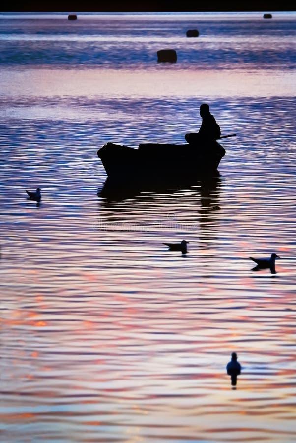 Sunset and silhouette of boatman. At Triveni Sangam confluence of three rivers, Kumbh Mela festival, Allahabad known as Prayagraj, Uttar Pradesh, India stock photography