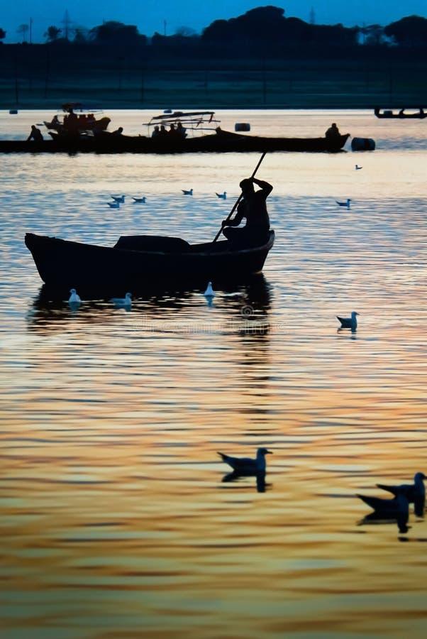Sunset and silhouette of boatman. At Triveni Sangam confluence of three rivers, Kumbh Mela festival, Allahabad known as Prayagraj, Uttar Pradesh, India royalty free stock image