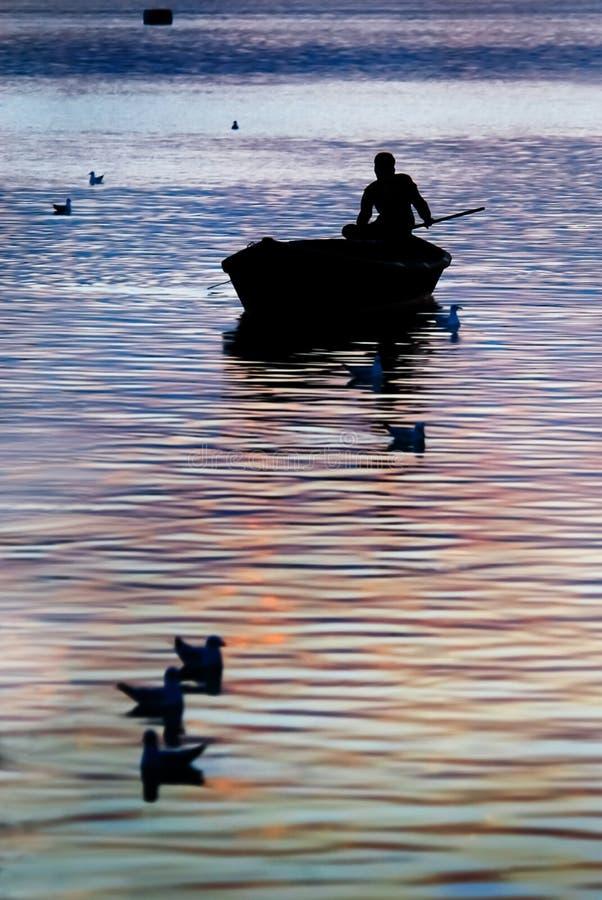 Sunset and silhouette of boatman. At Triveni Sangam confluence of three rivers, Kumbh Mela festival, Allahabad known as Prayagraj, Uttar Pradesh, India stock images