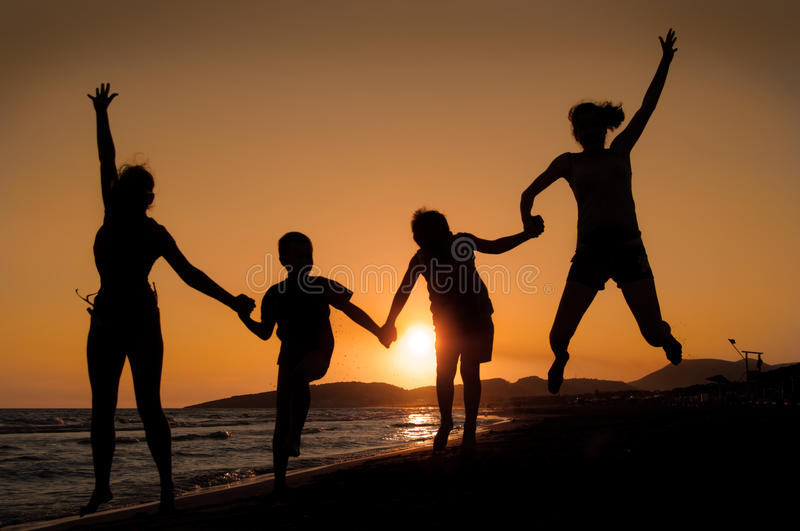 Sunset silhouette of family. Silhouette of family jumping on the beach on beautiful summer sunset stock photos