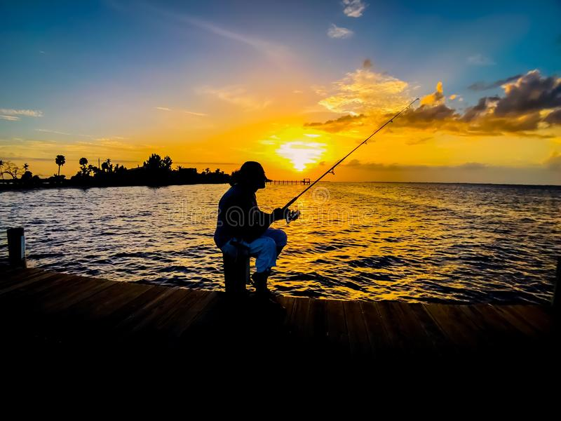 Sunset with Silhouette fishing on wooden pier in the sea royalty free stock photography