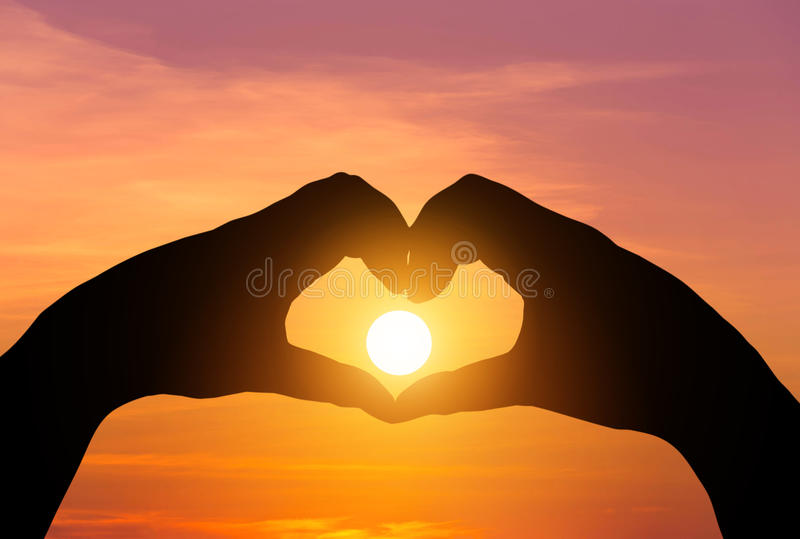 Sunset in the silhouette hands making heart shape stock images