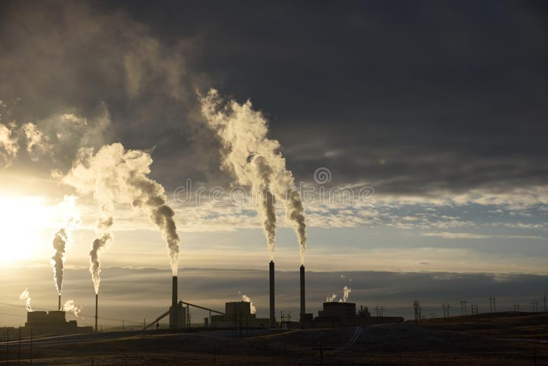 Sunset silhouette of smoke stack emissions rising from a coal-fired power plant stock photos