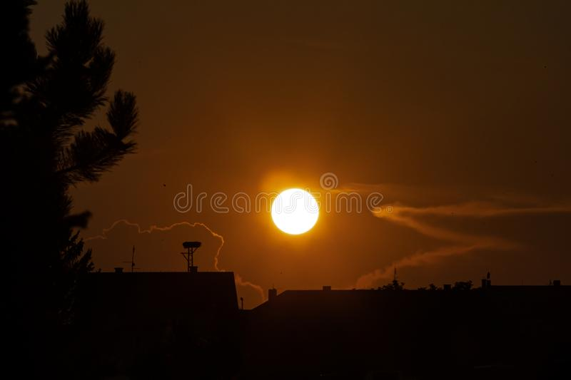 Sunset, silhouette of stork`s nest along with roofs of family houses. 1 stock photography
