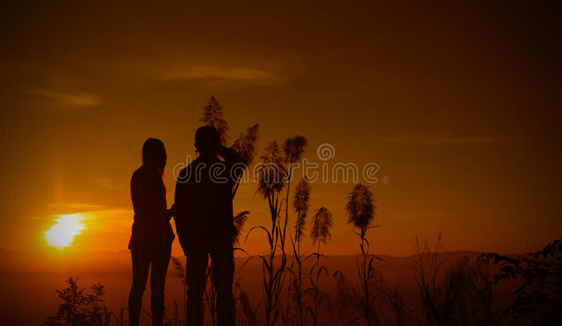 Sunset silhouette teen. Silhouette two teen look sunset royalty free stock photography