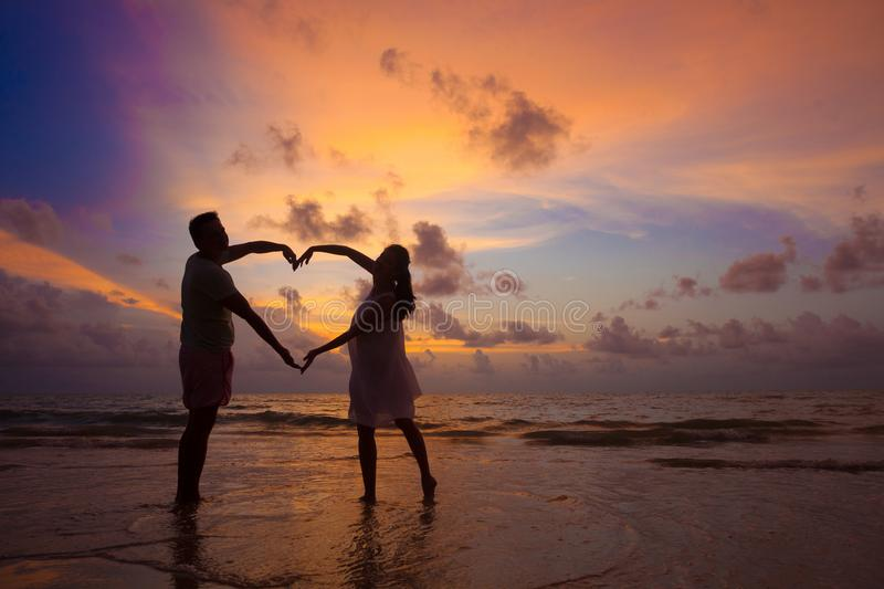 Sunset silhouette of young couple in love hugging at beach royalty free stock photography