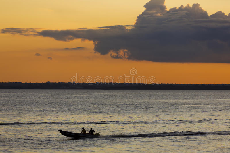 Sunset and silhouettes on boat cruising the Amazon River, Brazil. Sunset and silhouette of a two men sitting on a small wooden boat and cruising on the Amazon royalty free stock images