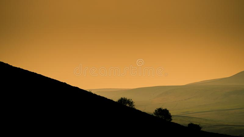 Sunset silhouettes the trees against green fields and orange sky at the Roaches in the Peak District stock photos