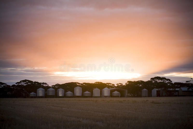 Sunset and Silo's. Sunset beams over grain silo's and fields stock photo