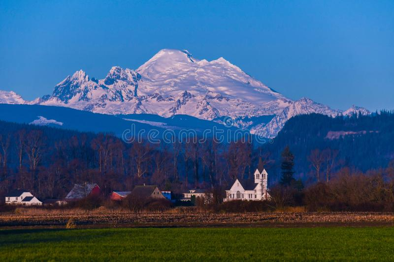 Sunset on Skagit Valley with Mount Baker in Background. Sun setting on Mount Baker from Skagit Valley with church in foreground royalty free stock image
