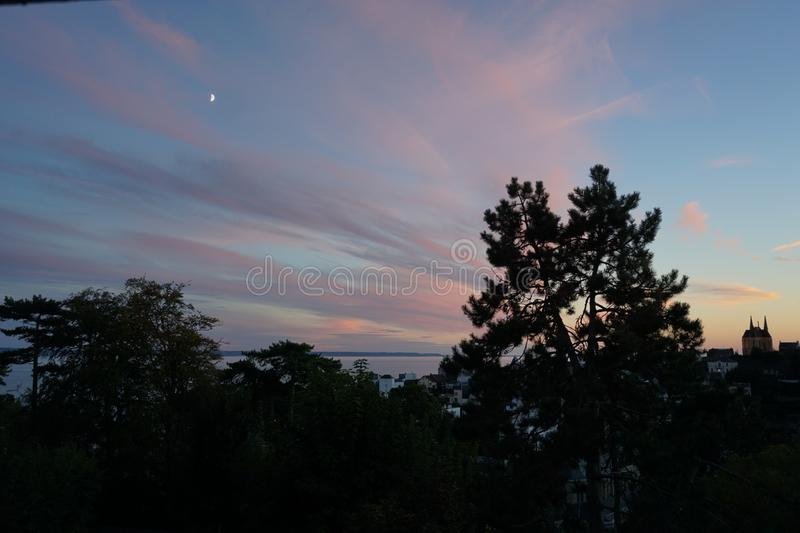 Sunset skies with sea view and trees and a church and a moon cresent. In afar stock image