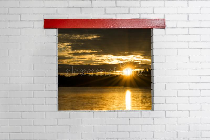 Sunset sky background. Dramatic gold sunset sky with evening sky clouds over the sea view from window on brick wall. Stunning sky stock images