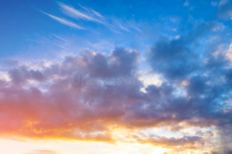 Sunset sky background - pink, orange and blue dramatic colorful clouds lit by evening sunset light. Vast sunset sky landscape scene stock photos