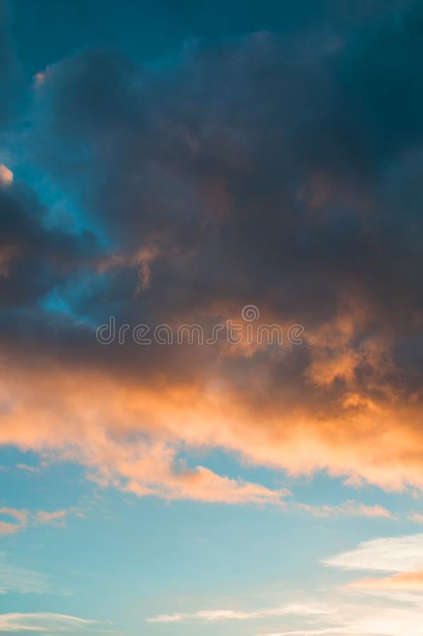 Sunset sky background -pink, orange and blue dramatic colorful clouds lit by evening sunshine. Vast sunset sky landscape. Sunset colorful sky background - pink royalty free stock images