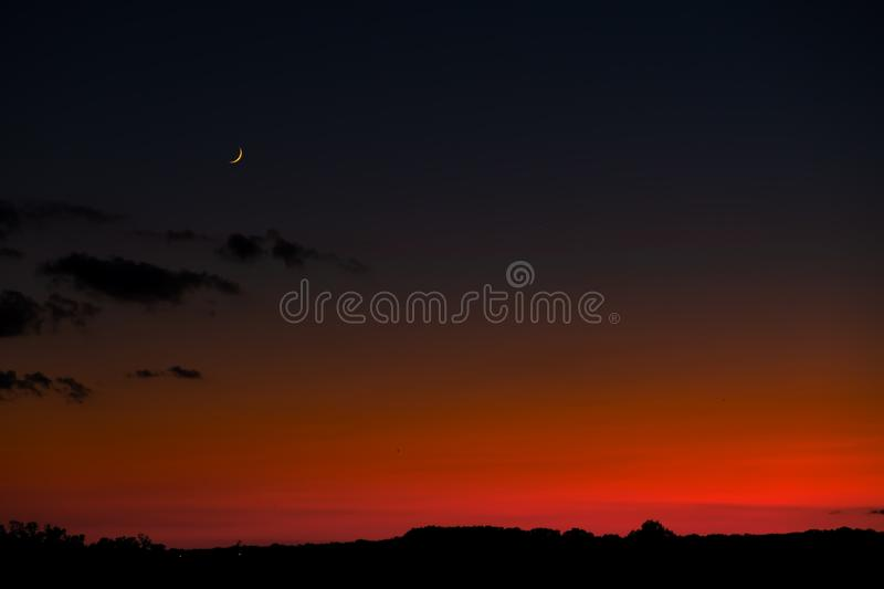 Sunset sky with bright red horizon and crescent moon.  royalty free stock photos