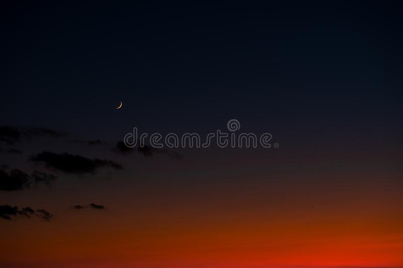Sunset sky with bright red horizon and crescent moon.  stock image