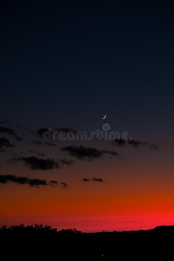 Sunset sky with bright red horizon and crescent moon.  royalty free stock photo