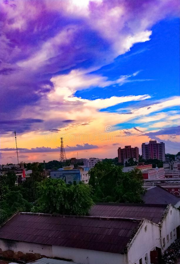 Sunset sky in city with buildings telephone towers and trees taken from a building balcony . stock image
