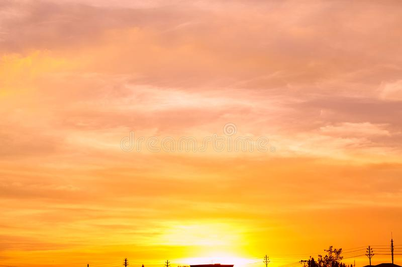 Sunset sky clouds trees orange. Colorful abstract background with fiery orange sky and clouds at sunset royalty free stock image