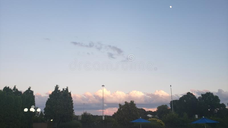 Sunset sky at night in Ohio with moon and tree stock photography