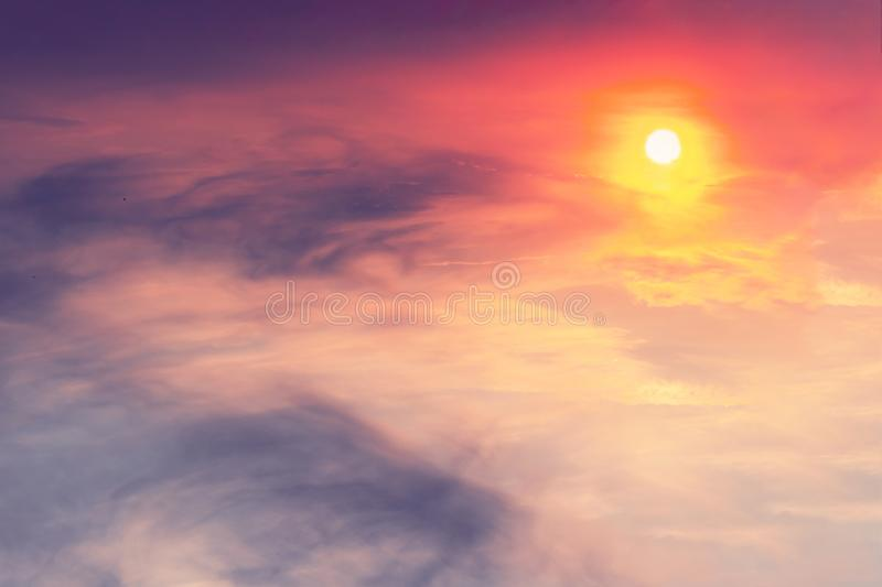 The sunset in the sky is pink-orange with purple clouds in the form of stains on which the sun shines. Landscape concept.  stock images