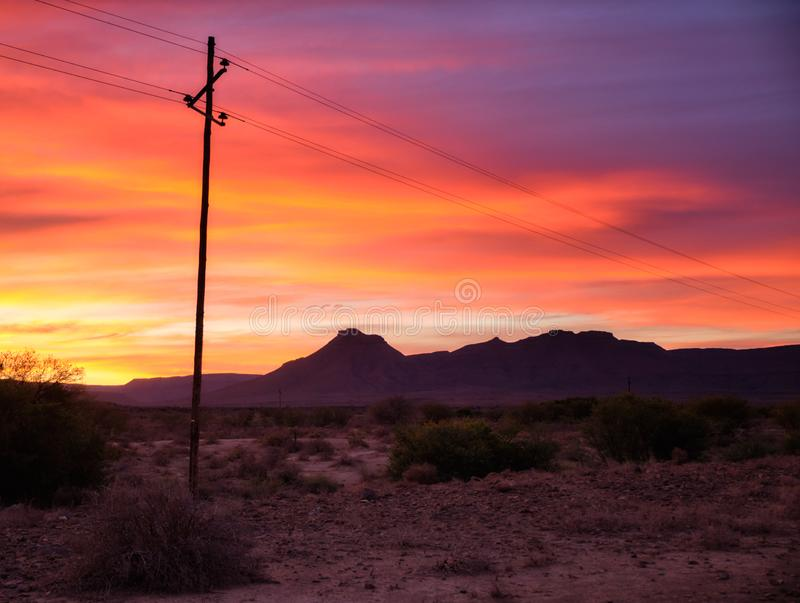 Sunset sky in wild Great Karoo. Sunset sky of orange and yellow in the vast Karoo of South Africa. With silhouette of telephone pole and wires leading to stock image