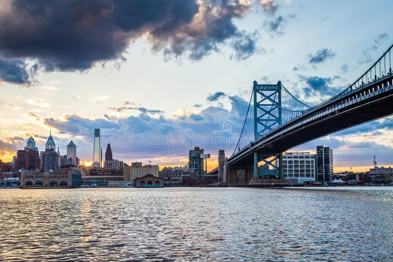 sunset skyline of philadelphia pennsylvania from camden new jersey with benjamin franklin bridge royalty free stock image
