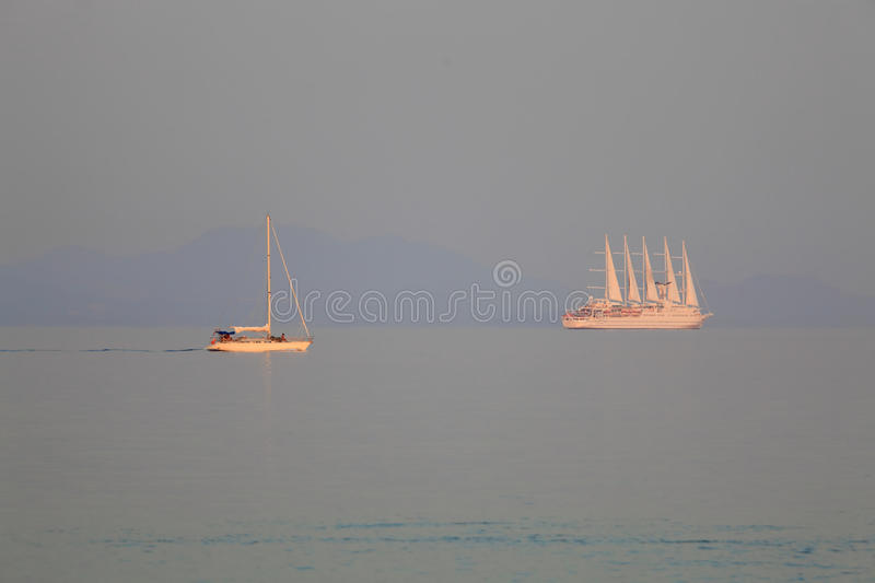Sunset with Small Yacht and Big Cruise Ship royalty free stock photography