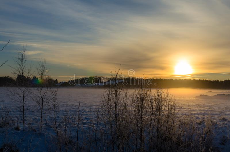 Sunset on a snowy farm. Winter in Turi, Jarvamaa County, in central Estonia royalty free stock image