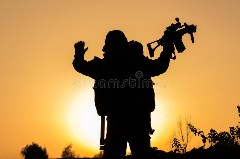 Sunset of soldier crouched in uniform stock image