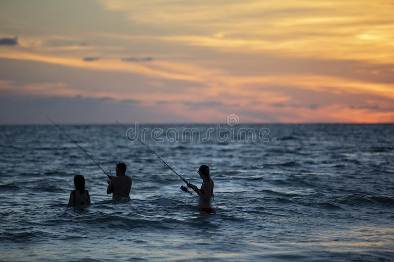 Sunset at St.Pete`s beach. Cloudy sunset at St.Pete`s beach and silhouetted people fishing in the ocean royalty free stock photography