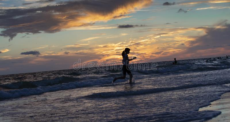 Sunset at St.Pete`s beach. Cloudy sunset at St.Pete`s beach and silhouetted young woman running in the ocean waves stock images