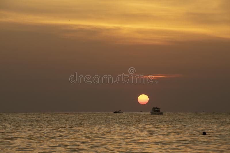 Sunset at St.Pete`s beach. Deep orange sky and sun with reflection on the water. Boat silhouette on horizon stock image