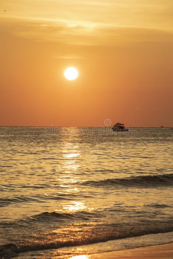 Sunset at St.Pete`s beach. Deep orange sky and sun with reflection on the water. Boat silhouette on horizon royalty free stock photo