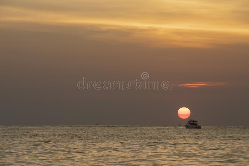 Sunset at St.Pete`s beach,. Deep orange sky and sun with reflection on the water. Boat silhouette on horizon stock photos