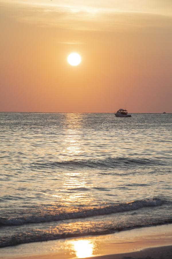 Sunset at St.Pete`s beach. Pink and orange sky and sun with reflection on the water. Boat silhouette on horizon royalty free stock photography
