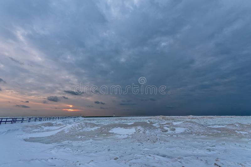 Sunset at Stearns Park in Ludington, MI. Frozen foreground leads to water and a sunset on Lake Michigan at Ludington`s North Breakwater Light at Stearns Park stock photos