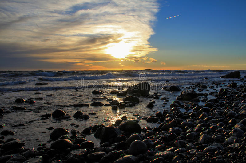 Sunset on a stone beach royalty free stock image