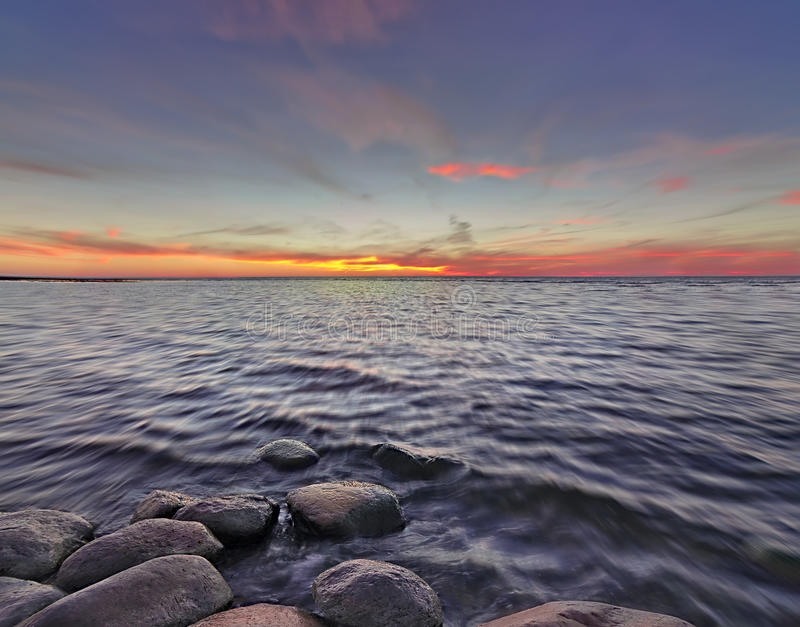 Sunset with stones on the lake royalty free stock photo