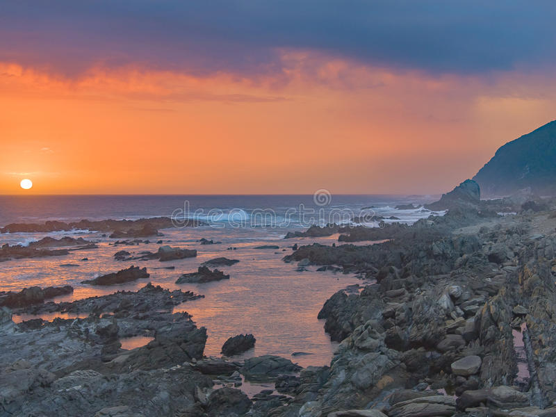 Sunset at Storms River, Tsitsikamma, South Africa. Beautiful Orange sunset and approaching thunderstorm, captured at Storms River mouth, Tsitsikamma region in stock image