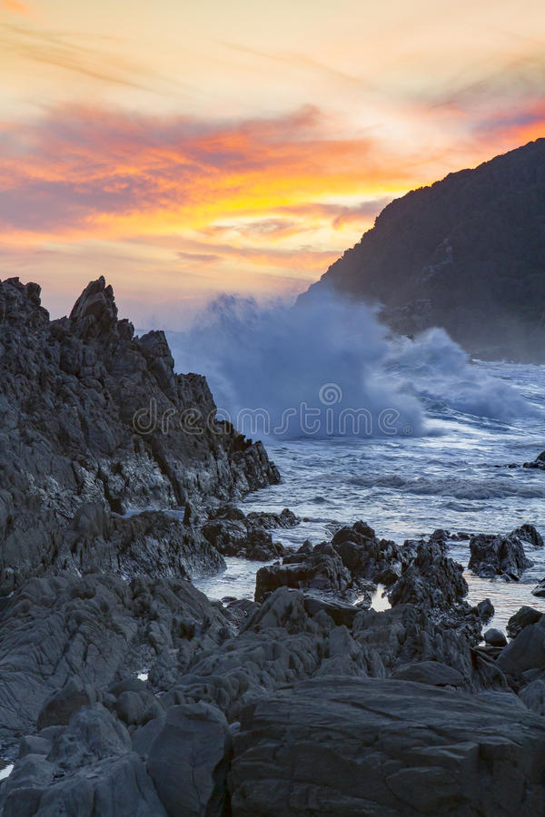 Sunset at Storms River, Tsitsikamma, South Africa. Beautiful Orange sunset and approaching thunderstorm, captured at Storms River mouth, Tsitsikamma region in royalty free stock image