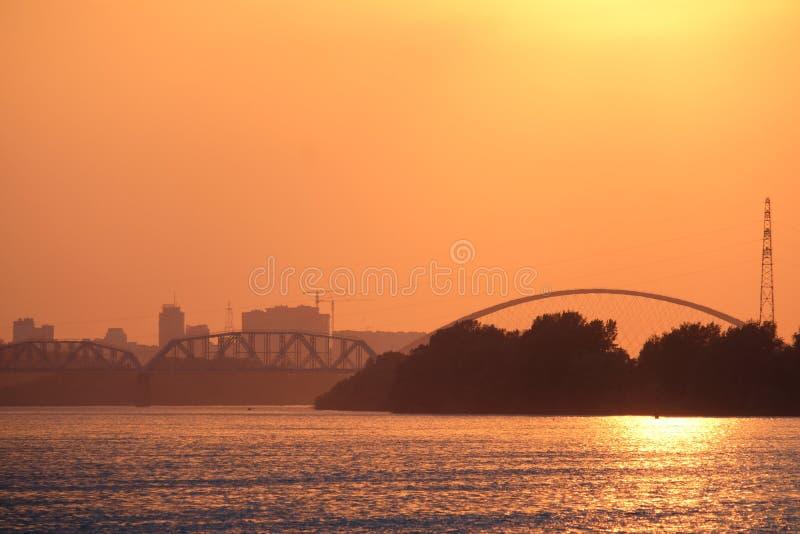 Ярко-красный закат на реке. Вдали виден мост. Вечерний закат. stock photos