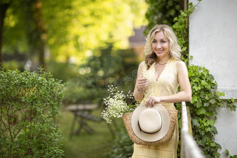 Sunset in summer.Rural life.A young woman with a basket,a bouquet of wildflowers and a hat standing in the background of the stock photography