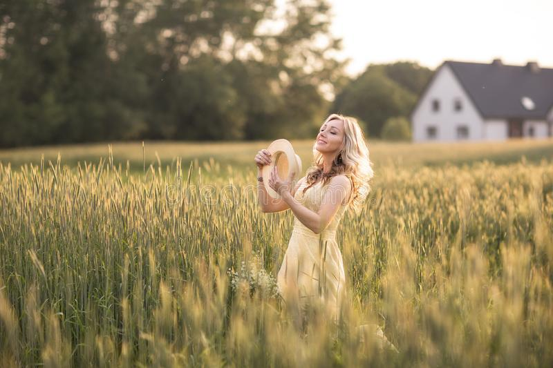 Sunset in summer.Rural life.A young woman in the field throws a hat. Rustic style stock images