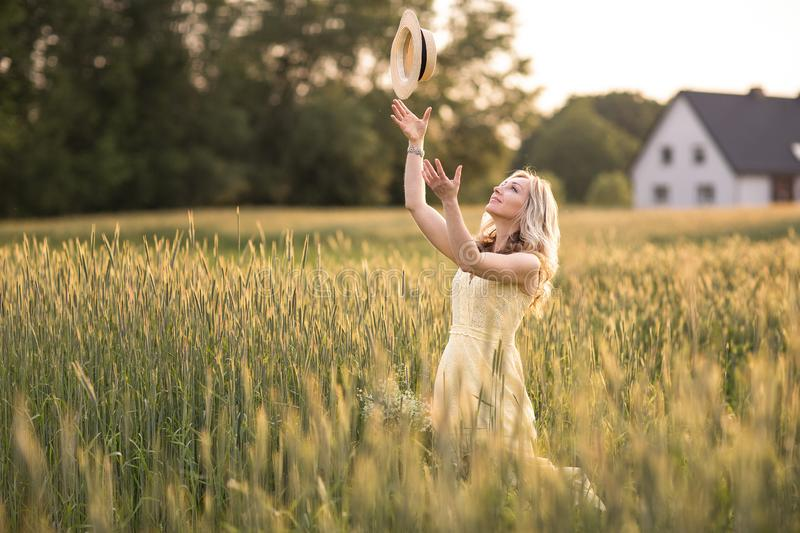 Sunset in summer.Rural life.A young woman in the field throws a hat. Rustic style royalty free stock photography