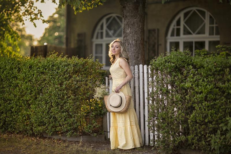 Sunset in summer.Rural life.A young woman leaves the house.Female portrait on the background of the house near the gate. stock photo