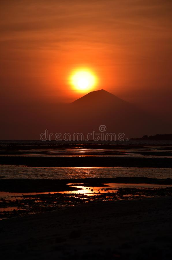 Sunset with sun above mount Agung on Bali. Sunset with the sun above mount Agung on Bali. Volcano silhouette, vibrant colors, dramatic landscape stock image