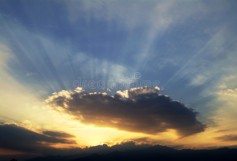 Sunset - The sun across clouds royalty free stock images