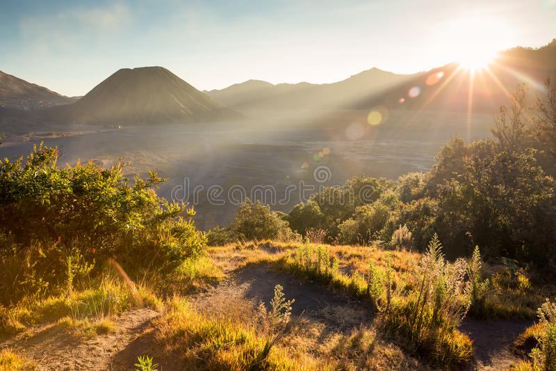 Before sunset with sun-flare at Mount Bromo volcano, the magnificent view of Mt. Bromo located in Bromo Tengger Semeru National P. Ark, East Java, Indonesia stock photo