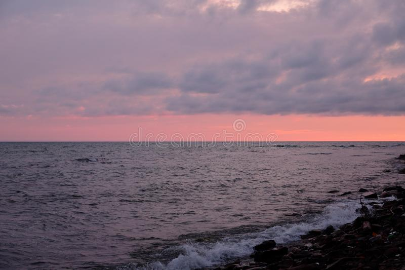 Sunset, the sun`s rays make their way through the heavy clouds and illuminate the summer, troubled sea royalty free stock photo
